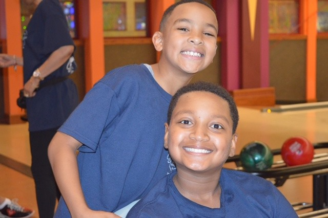 Two kids smiling by bowling ball return
